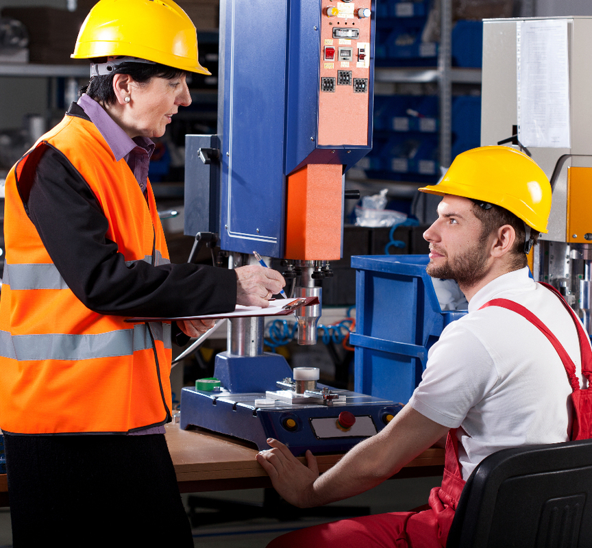 A ergonomist interacting with a worker in a machine shop to highlight the role of ergonomists in MSD prevention.