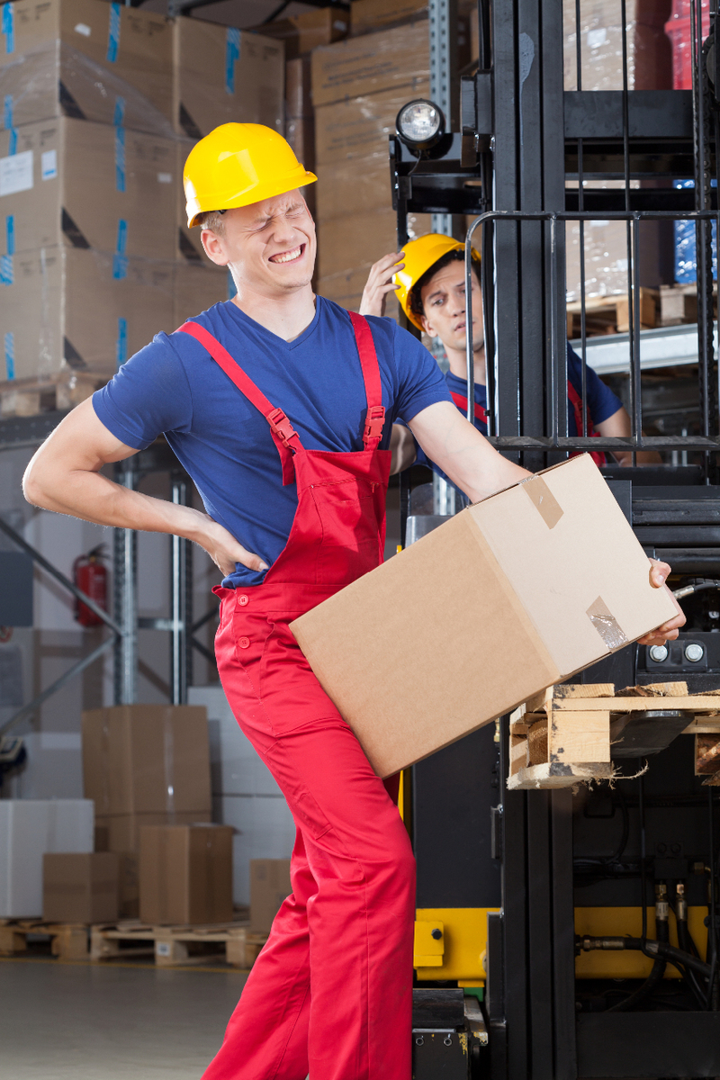 Worker lifting a box and holding his low back area to indicate he is experiencing pain