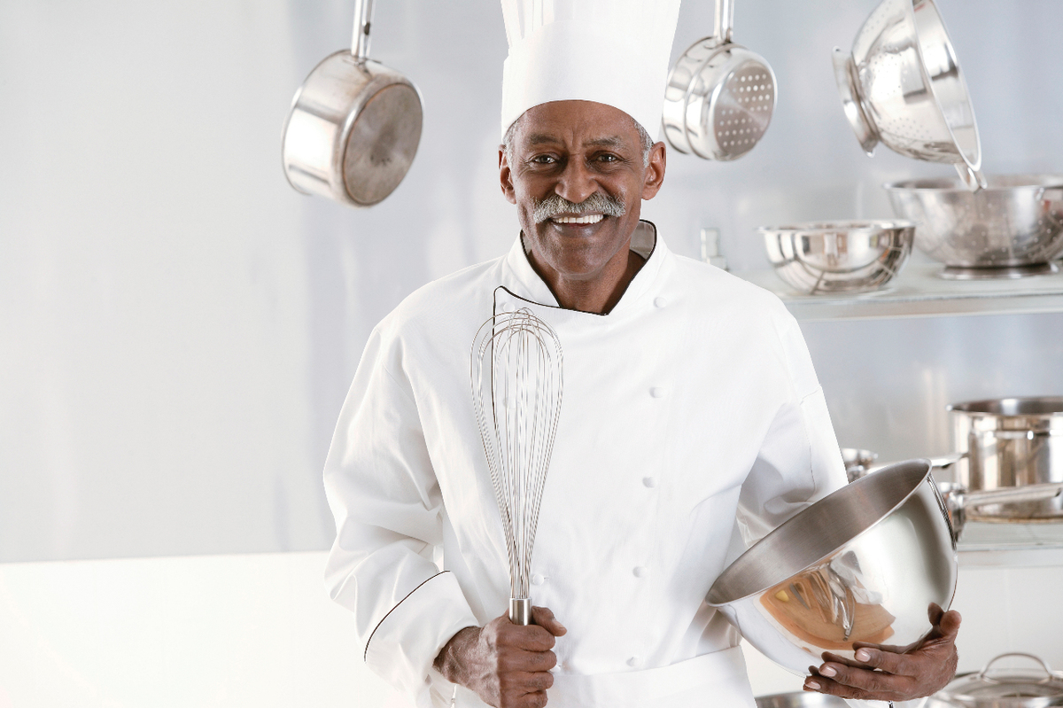 Image depicting a man wearing a chef's uniform to highlight a small business owner.
